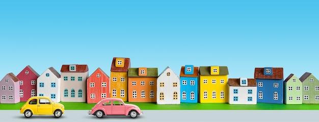 거리를 따라 귀여운 집들이 줄지어 있고 복고풍 장난감 자동차가 있는 마을 풍경. 푸른 하늘이 있는 거리와 집들