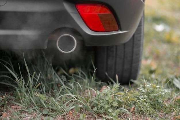 芝生に駐車した車の排気管からの有毒なco2排気ガス。