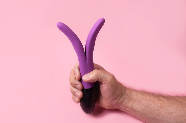 Toy for adultsdildo in hand on a pink wall