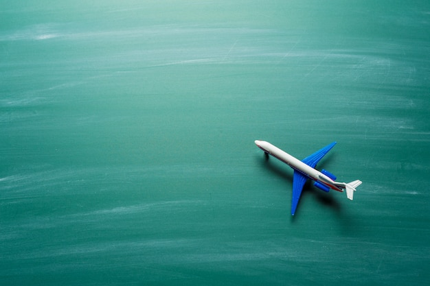 Toy airplane over chalkboard background