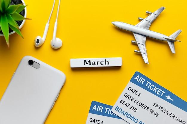 3月の春の休日の概念として黄色の背景におもちゃの飛行機。