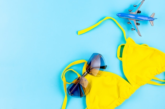 Toy airplane, swimsuit and glasses on a blue table