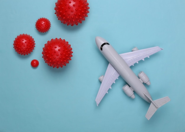 Toy airplane with virus strain models on a blue. travel during the pandemic covid-19