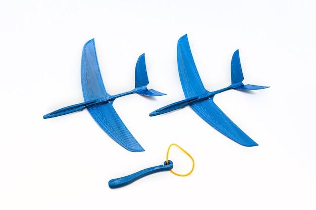 輪ゴム、白い背景で発売されたおもちゃの飛行機