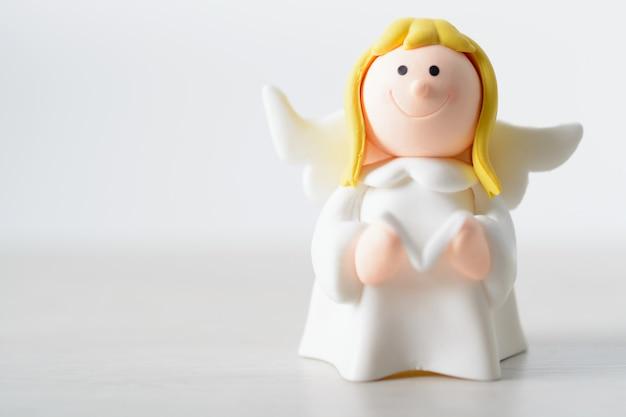 Игрушечный ангел с книгой на белом фоне