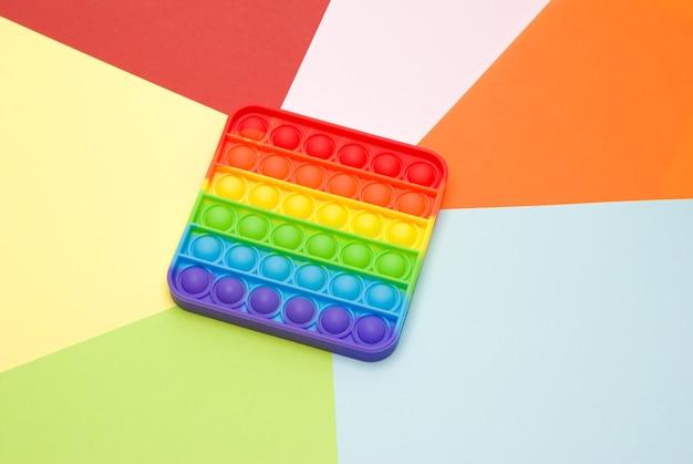 Игрушка-антистресс поп-он изолирован на разноцветной поверхности