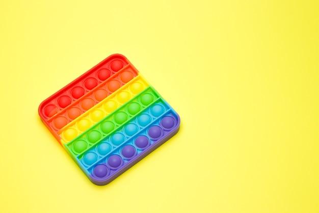 Игрушка-антистресс поп-он изолирован на желтой поверхности