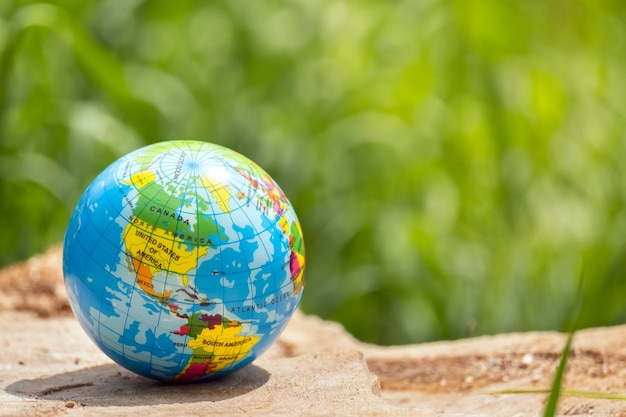Toy ball, globe of the planet earth on a wooden stump in a forest on a green grass background. travel around the world, tourism, ecology concept with copy space.
