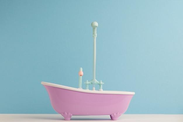 Игрушечная ванная комната с душем для куклы на синей стене. мытье и купание младенцев. гигиена и уход за маленькими детьми.