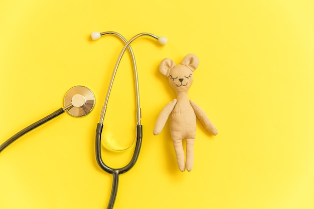 黄色の背景に分離されたおもちゃのクマと医療機器聴診器
