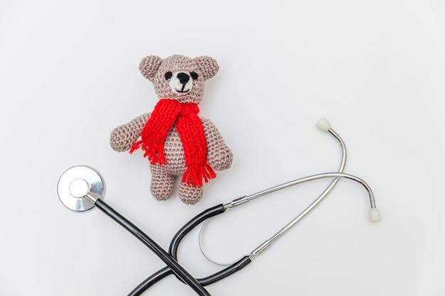 白い背景で隔離のおもちゃのクマと薬の聴診器