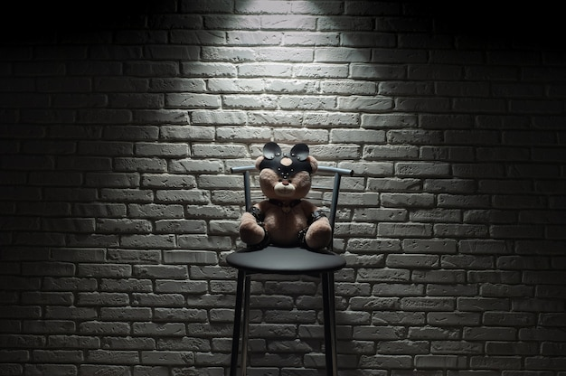 The toy bear dressed in leather straps accessory for bdsm games in hard light against a brick wall
