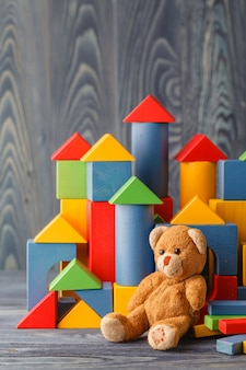 Toy bear and pile wooden building blocks
