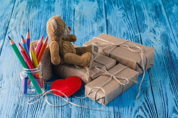 Toy bear and some paper parcels wrapped on wooden table