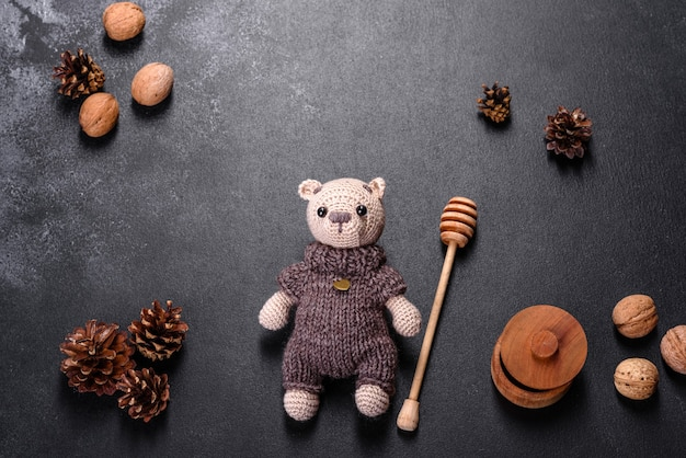 Toy bear tied from woolen threads on a dark table. manual work, hobby