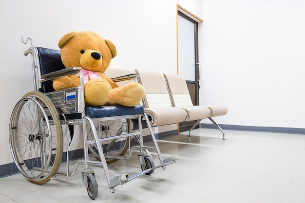 A toy bear on a wheel chair