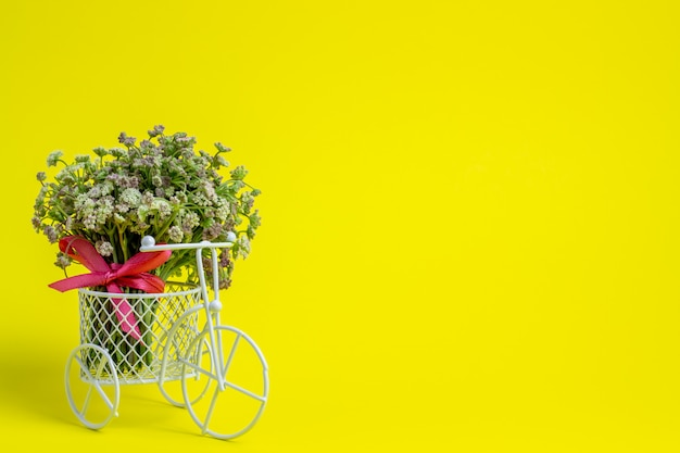 A toy bike carries a flowers.