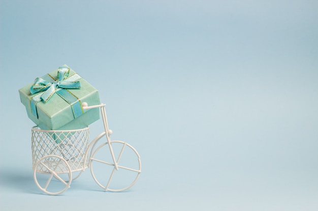 A toy bike carries a gift. the idea for a postcard. blue  . minimalism.