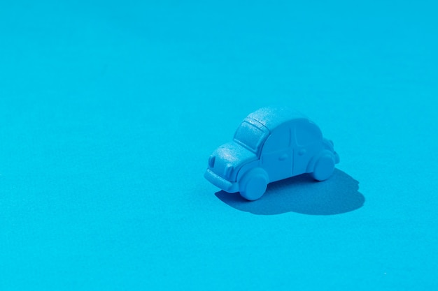 Игрушечная синяя машинка на голубом. понятие о продаже и покупке автомобилей.