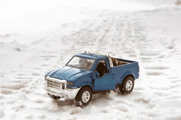 겨울 숲의 장난감 파란색 픽업 자동차는 도로에 서 있습니다. 픽업 트럭에는 크리스마스 트리 콘이 있습니다.