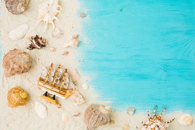 Toy boat and seashells among sand on board