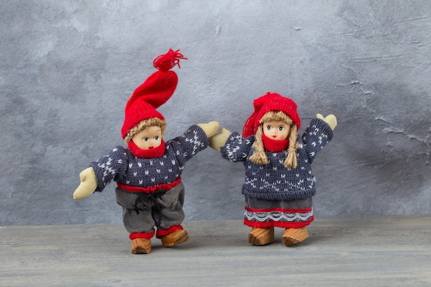 A toy boy and girl in winter clothes hold hands
