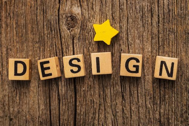 Игрушечные кирпичи на столе со звездой и словом дизайн