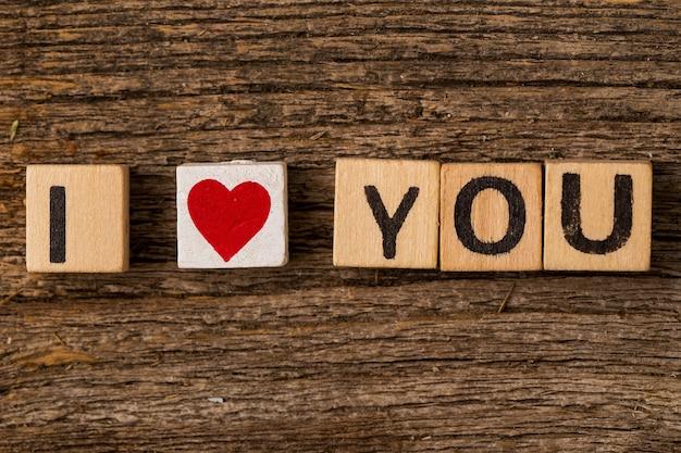 Игрушечные кирпичи на столе с цитатой я тебя люблю