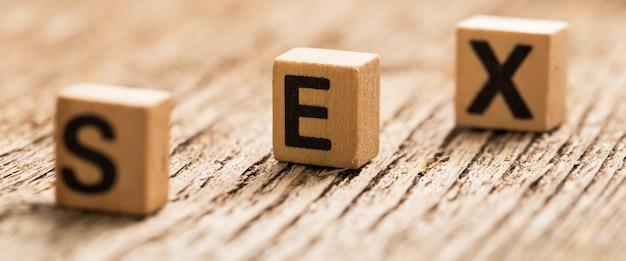 Игрушечные кубики на столе со словом секс
