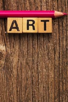 単語アートとピンクの鉛筆でテーブルの上のおもちゃのレンガ