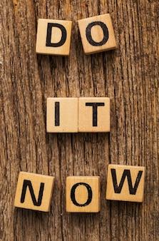 Игрушечные кирпичи на столе со словом «сделай это сейчас»