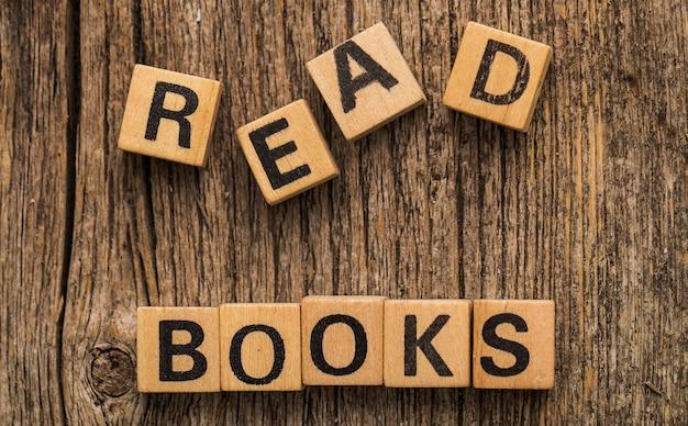 単語を読んだ本とテーブルの上のおもちゃのレンガ