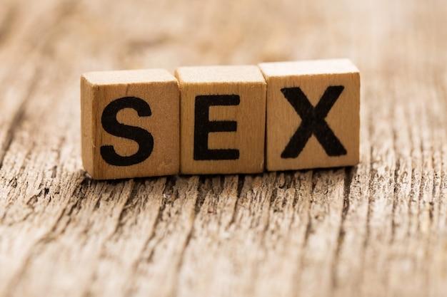 単語のセックスとテーブルの上のおもちゃのレンガ