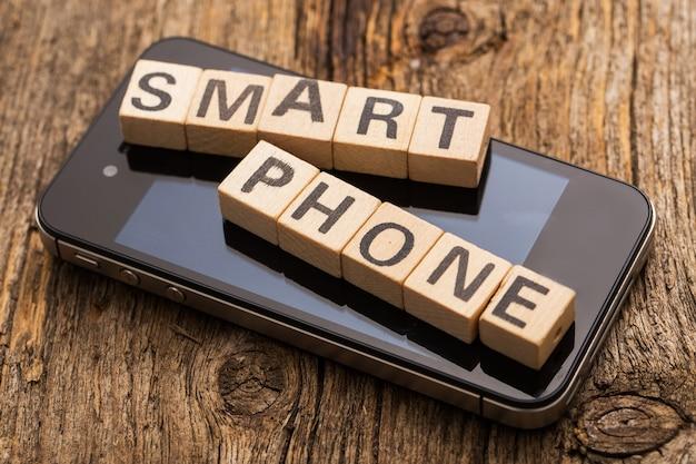Игрушечные кирпичи на столе со словом смартфон