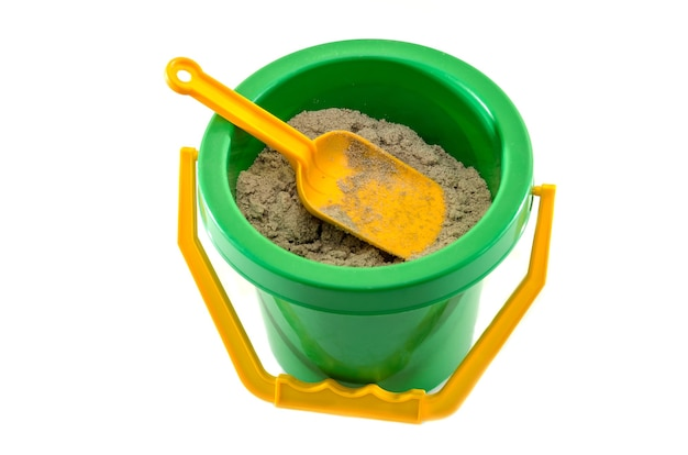 Toy bucket with sand and a shovel on white surface