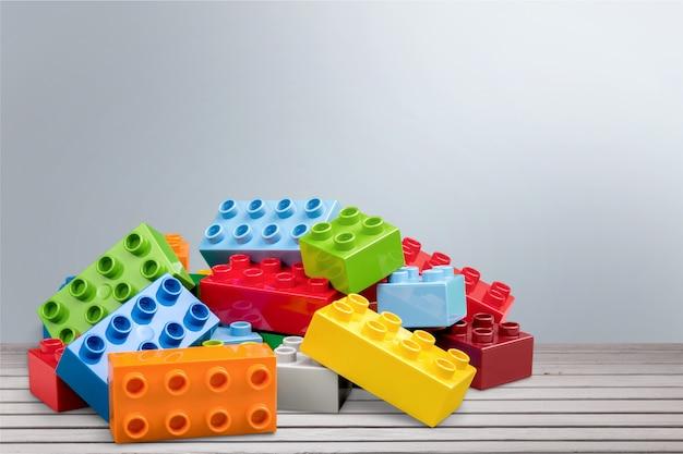 背景にレンガを構築するカラフルな子供たちを構築するおもちゃ
