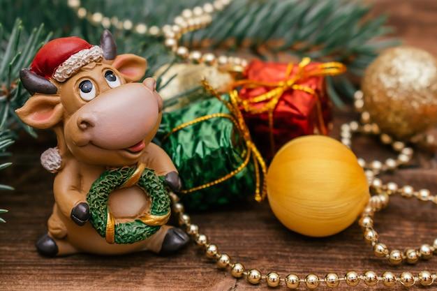 산타 클로스 모자에 장난감 황소. 작은 선물 상자와 공 크리스마스 트리 분기.