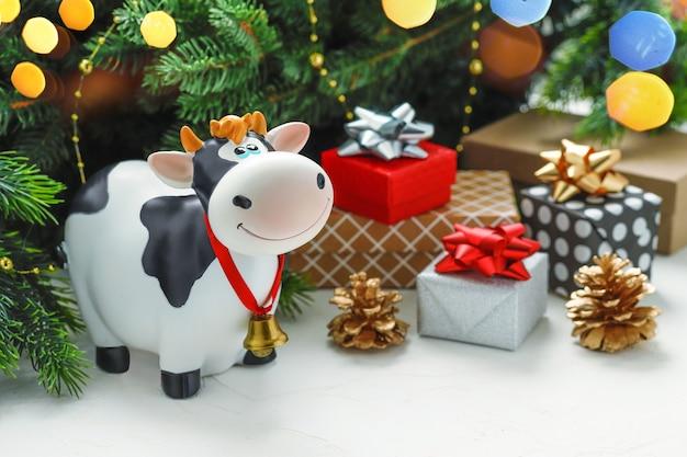 モミの枝の背景に贈り物とおもちゃの雄牛