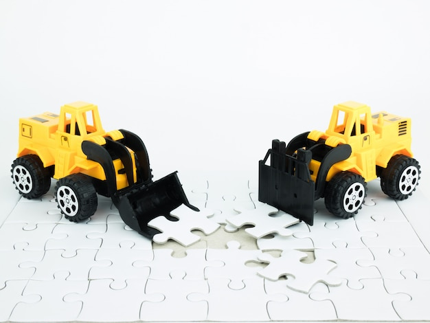 Toy bulldozer and forklift with jigsaw puzzle on white background