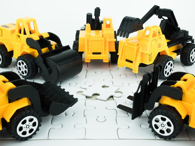 Toy bulldozer, pressure road,  crane, forklift and jigsaw puzzle with teamwork