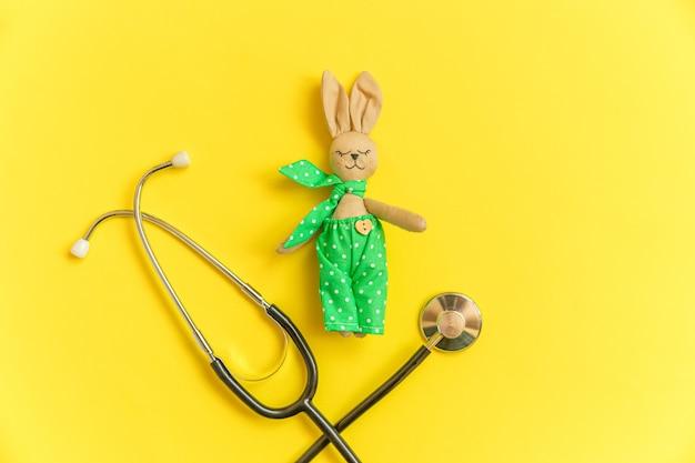 노란색 배경에 고립 된 장난감 토끼와 의학 장비 청진 기