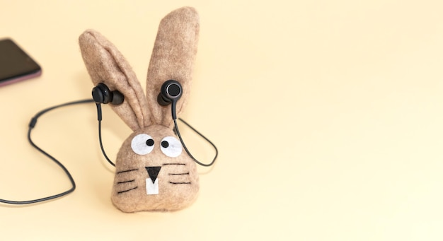 Toy bunny on a beige background in headphone. copy space.