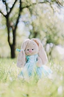 Игрушечный кролик в синем платье в зеленой траве