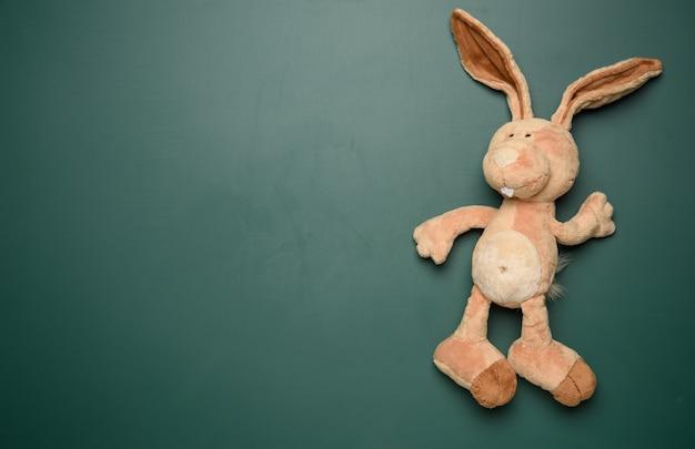Игрушечный кролик на школьной доске зеленым мелом, место для письма