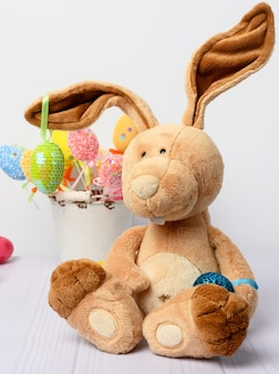 Toy bunny sitting and decorative colorful easter eggs