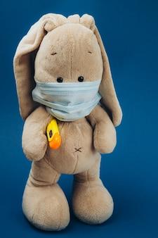 足の下と青い表面上のマスクの温度計とおもちゃのウサギ