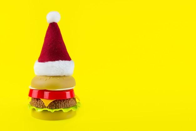 黄色の背景にサンタの赤い帽子とおもちゃのハンバーガー。クリスマスのファーストフード。