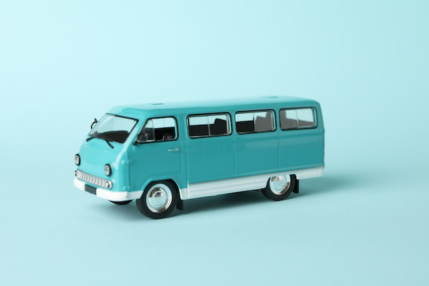 Toy bus on blue background, close up and space for text