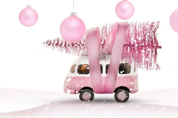 장난감 버스 자동차는 숲에서 크리스마스 트리를 운반합니다. 분홍색과 흰색 색상, 겨울 휴가 새해 분위기. 파노라마 공간을 복사합니다.