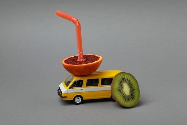 灰色の孤立した背景に果物とわらのおもちゃバス
